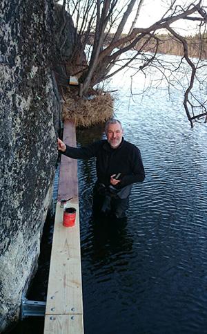 Christer Åstrand i färd med att måla den nya spången.